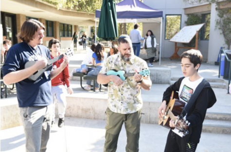 Mr. Lindsay, Rabbi David, and Zev Gaslin share music with their peers on the guitar and ukulele during 2.0neg.