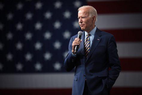 Joe Biden gives a speech beside a large American flag graphic