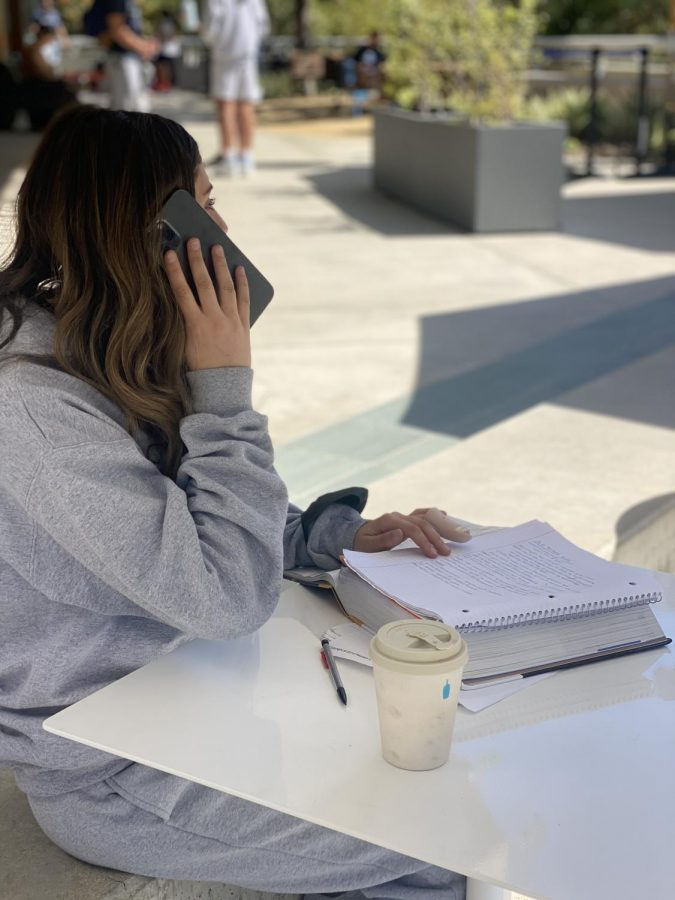 Noa Abromavitch '22 on the phone while doing homework